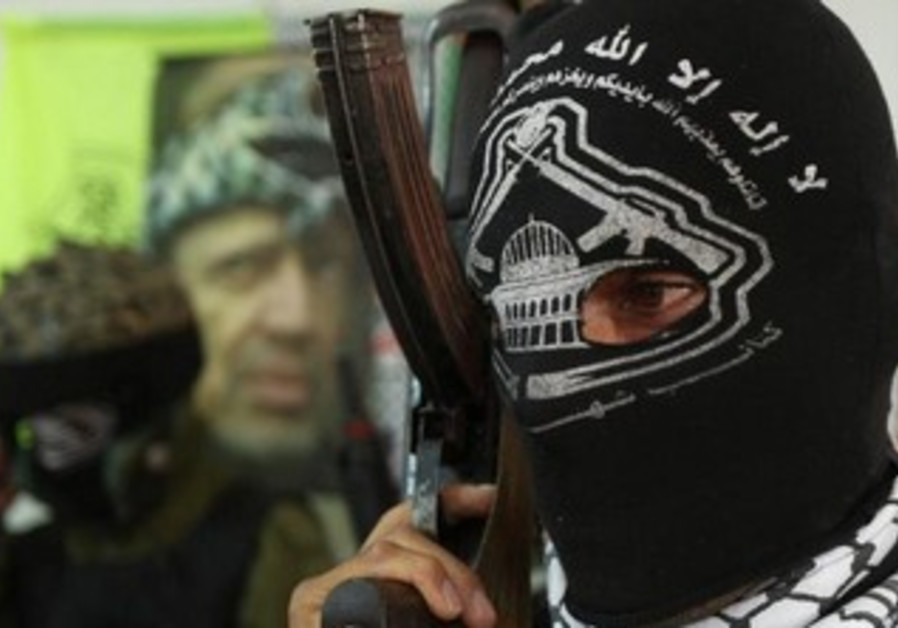A masked militant from Al-Aqsa Martyrs Brigades of the Fatah movement in Hebron, August 3, 2008.