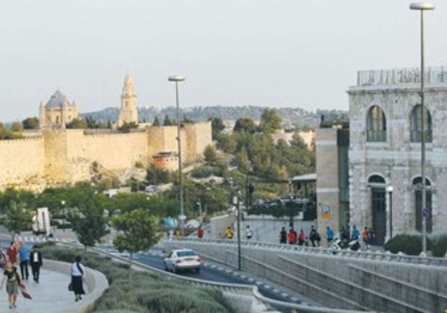 THE OLD CITY walls in east Jerusalem contrast against the modern buildings in west Jerusalem