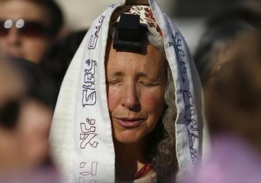 A Women of the Wall member dons tefillin and a tallit.