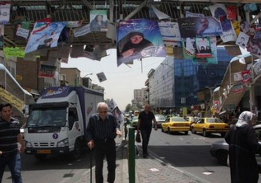 Pedestrians walk beneath election posters hanging off a pedestrian crossing in Tehran
