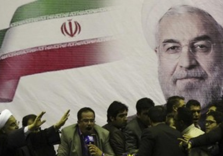 Iranian presidential candidate Hassan Rohani (L) waves to supporters