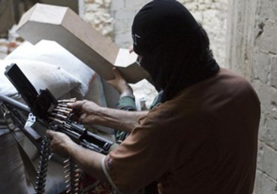 A Free Syrian Army fighter prepares his weapon