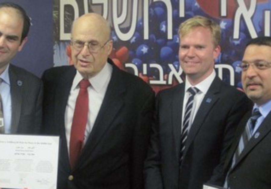 UNITED HATZALAH leaders Eli Beer (left) and Murad Alyan (far right) receive peace award.