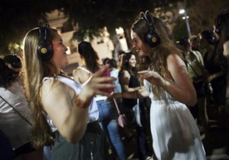 """Women dance during a """"Silent Disco"""", in Tel Aviv during the """"White Night"""" festival June 30, 2011"""