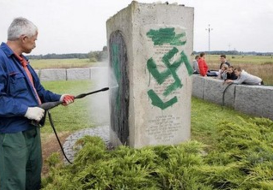 A Polish man cleans a monument in Jedwabne