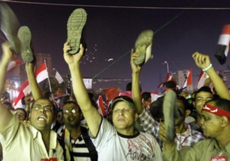 Anti-President Mohamed Morsi protesters hold up their shoes after a speech by Morsi