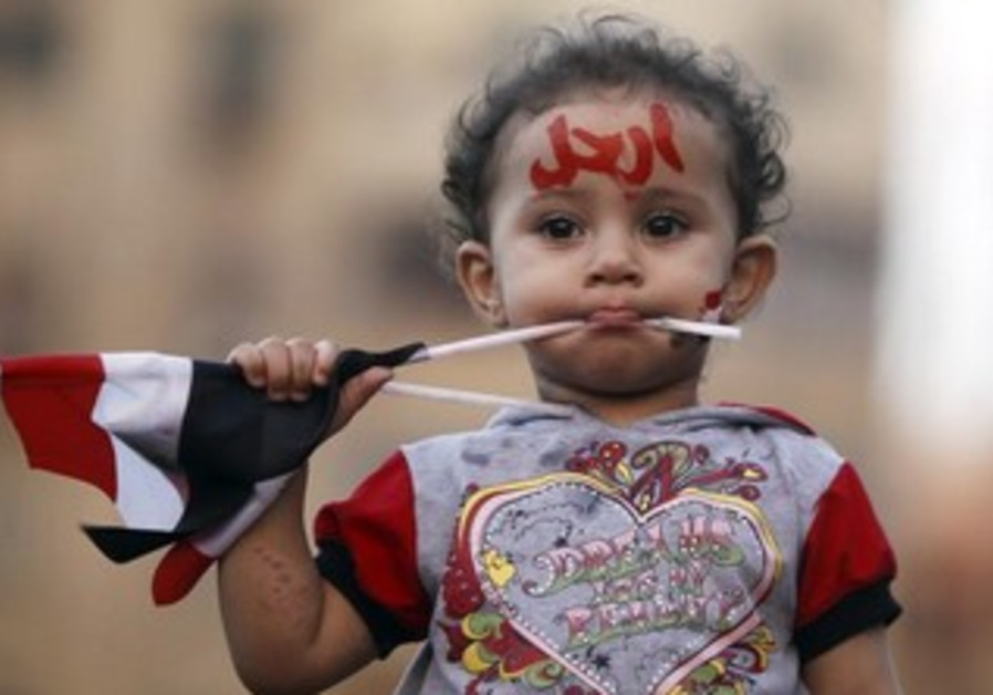 """A girl with the colours of the Egyptian flag and the word """"leave"""" painted on her face"""