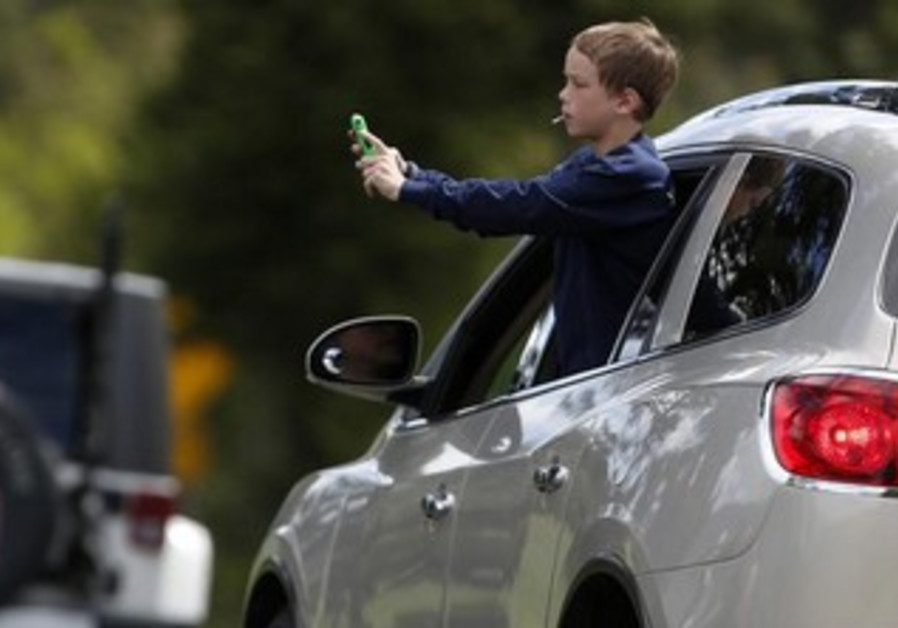 A child leans out the window of a car.