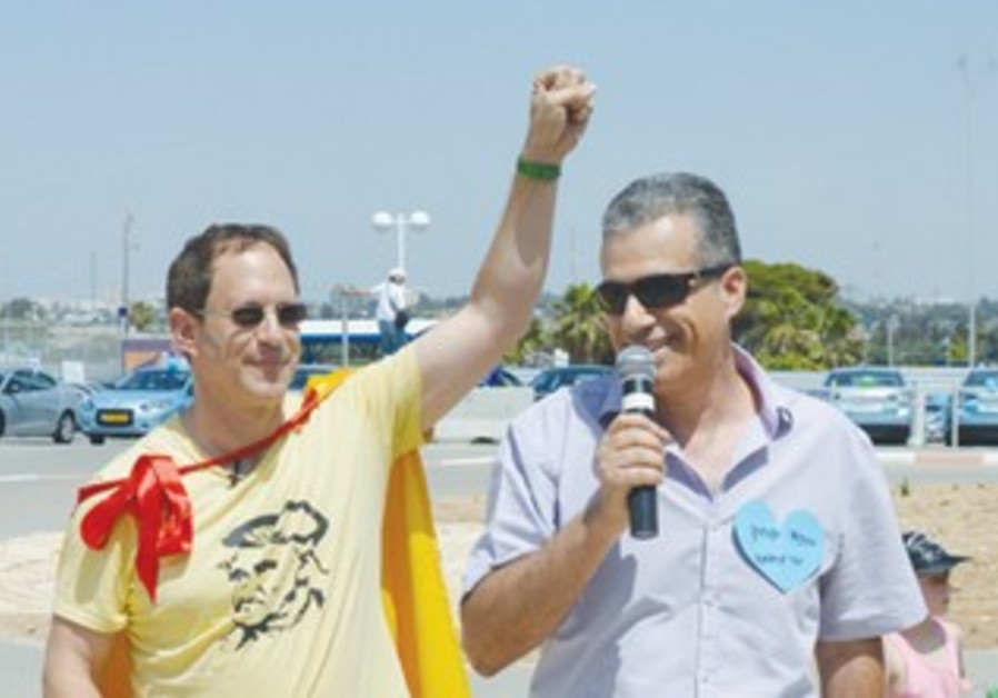 Yosef Abramowitz (left) and Efi Shahak attend a rally of Better Place clients in May.