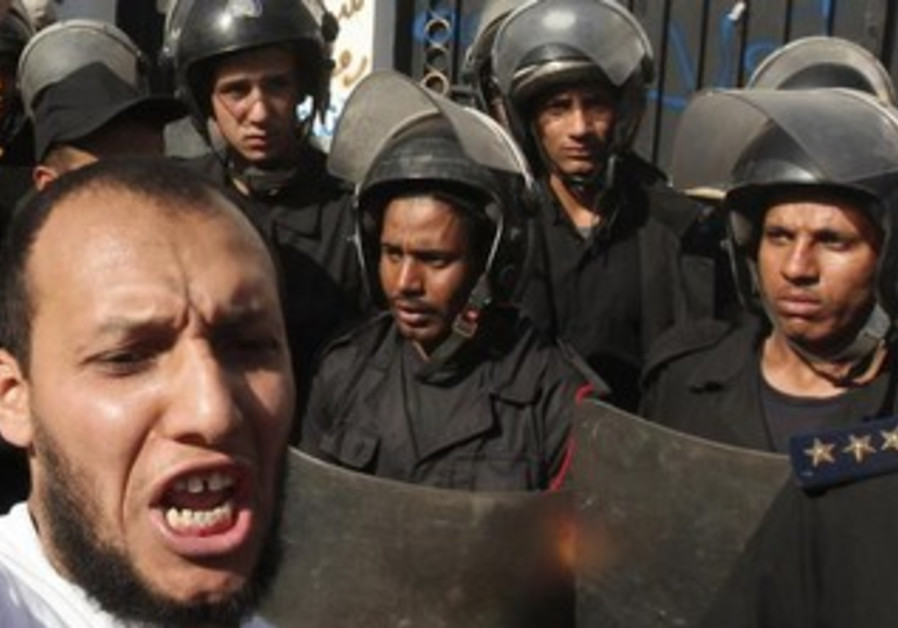Police stand guard near an Islamist protester outside the Iranian ambassador's house in Cairo.