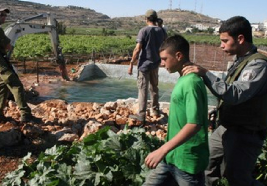 ISRAELI TROOPS stand guard as a Palestinian reservoir is destroyed near Hebron to stop water theft.