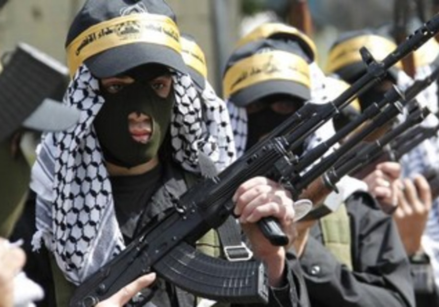 Palestinian Fatah members carry their weapons as they take part in a parade.