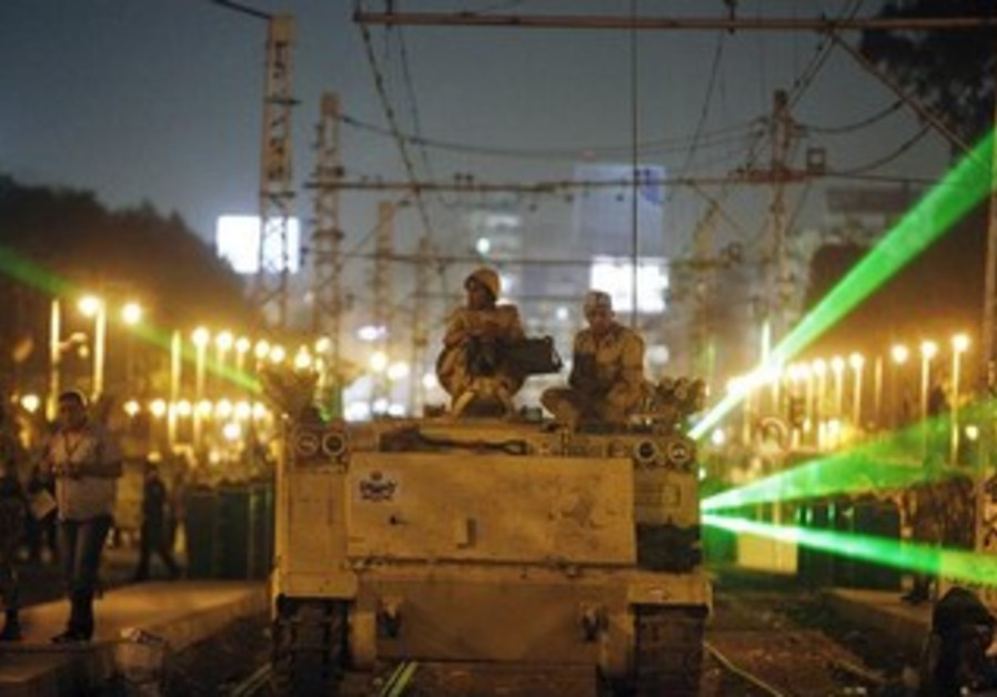 Egyptian Army soldiers sit on an armoured personnel carrier (APC)