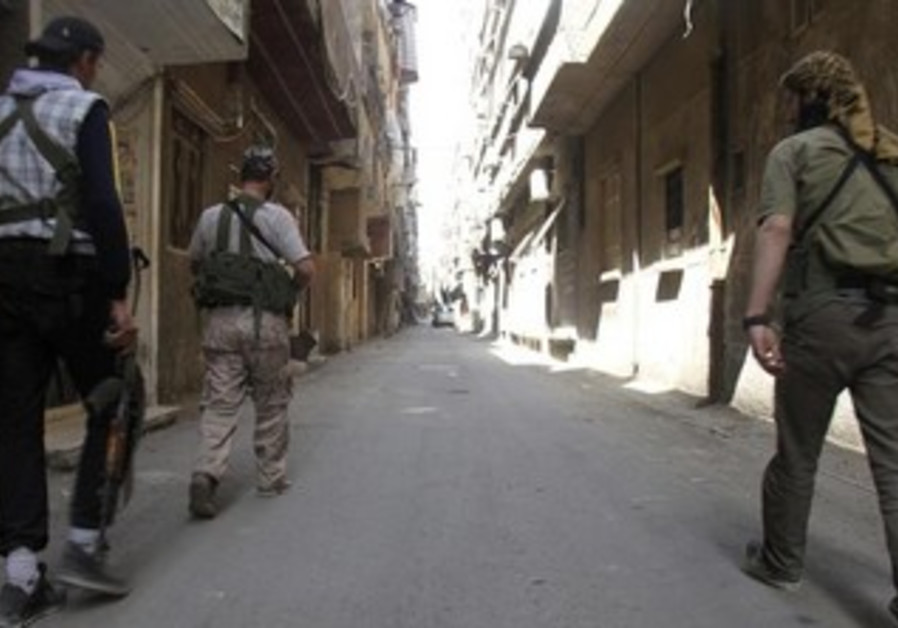 Free Syrian Army fighters walk along a street in the refugee camp of Yarmouk near Damascus, May 5.