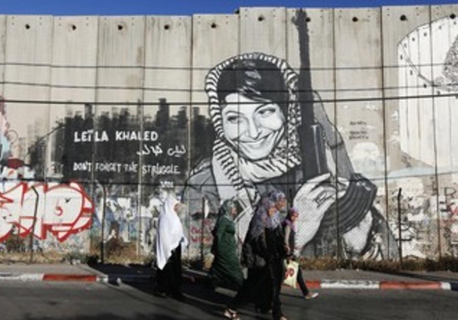 PALESTINIAN WOMEN walk past graffiti of convicted hijacker Leila Khaled in Bethlehem