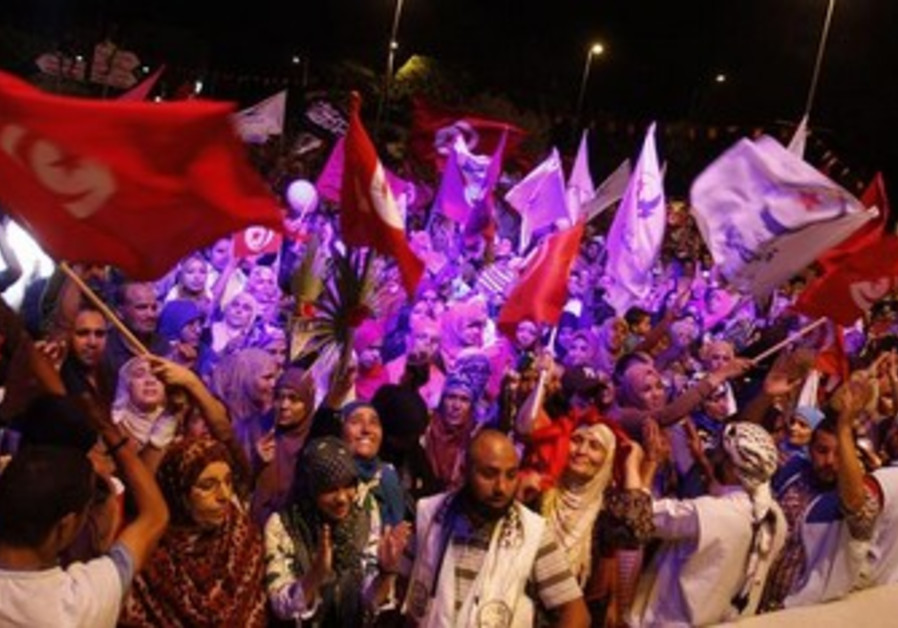 Supporters of the Islamist Ennahda movement wave flags in Tunis, August 2, 2013.