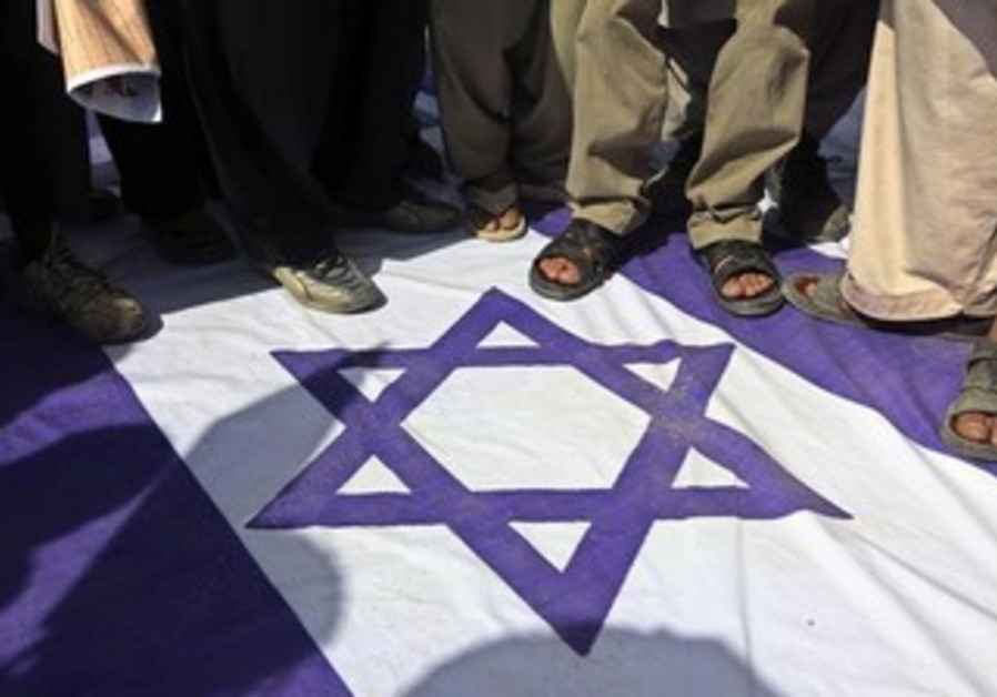 Demonstrators step on an Israeli national flag during a rally to mark Al-Quds (Jerusalem) Day.