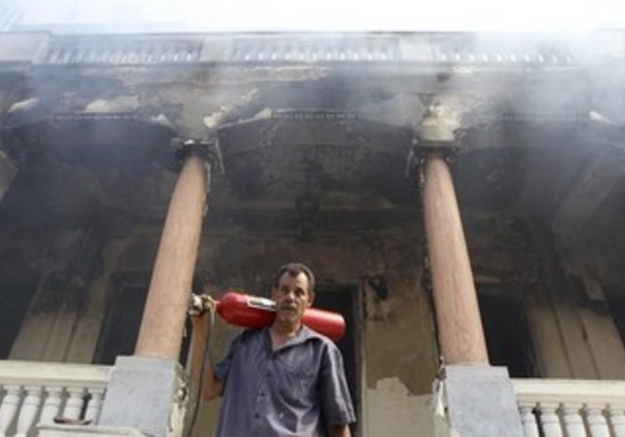 A man walks from a government building that was set ablaze in Giza's district of Cairo, August 15