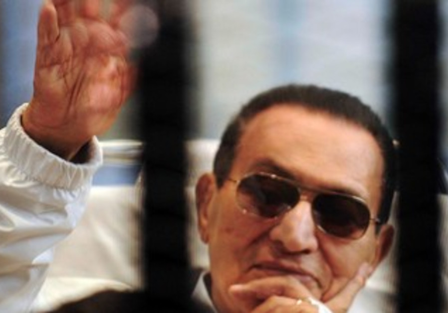 Former Egyptian President Hosni Mubarak waves to his supporters in a Cairo courtroom, April 2013.