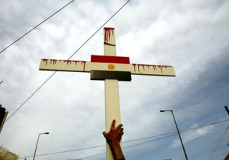 An Egyptian Coptic Christian holds a cross with the Egyptian flag.