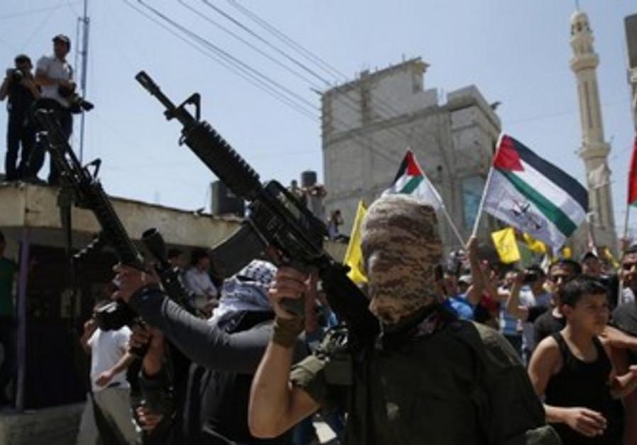 Palestinian militants holding weapons during funerals at Qalandiya Refugee Camp, Ramallah August 26.