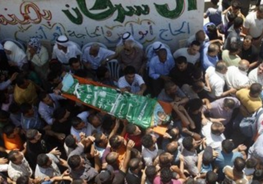 Palestinians carry body of Ibrahim Sarhan during his funeral in refugee camp, Nablus July 13, 2011.