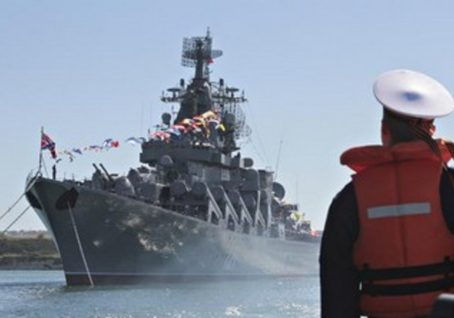 A sailor looks at the Russian missile cruiser Moskva moored in the Ukrainian Black Sea