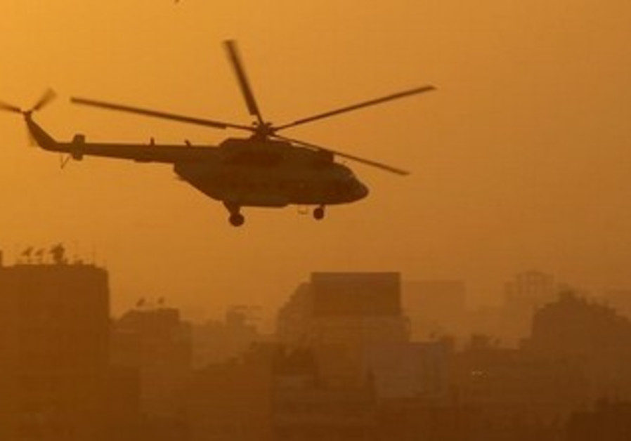 An Egyptian military helicopter flies during sunset over Tahrir Square.