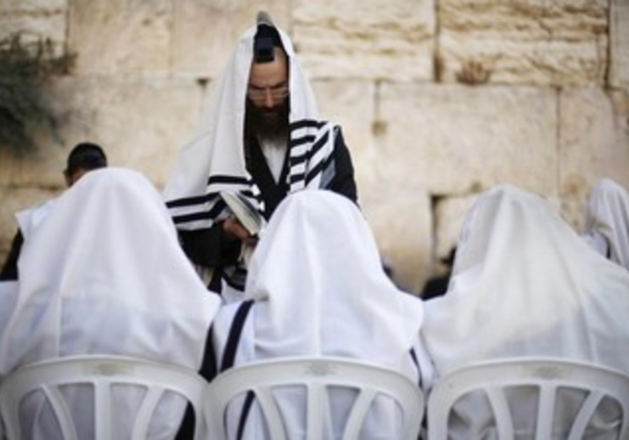 Jewish worshippers covered in prayer shawls pray at the Western Wall.