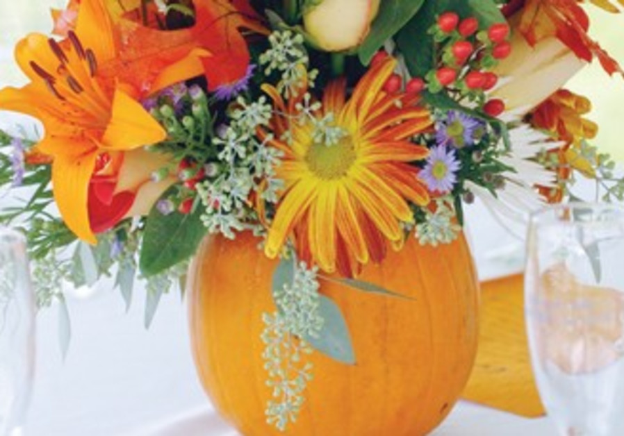 A SMALL pumpkin makes a colorful base for a floral centerpiece