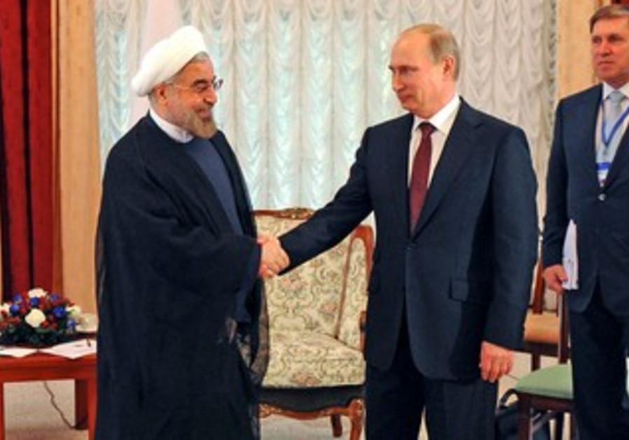 Putin and Rouhani shake hands.