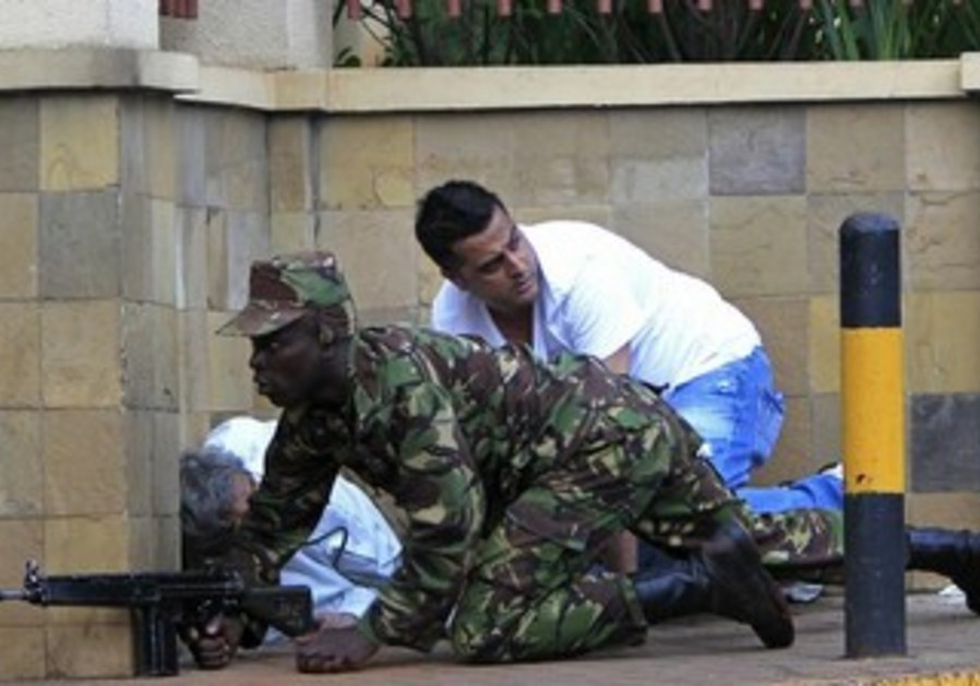 Kenyan soldier takes cover outside Nairobi mall where 59 were killed in terror attack, Sept 21