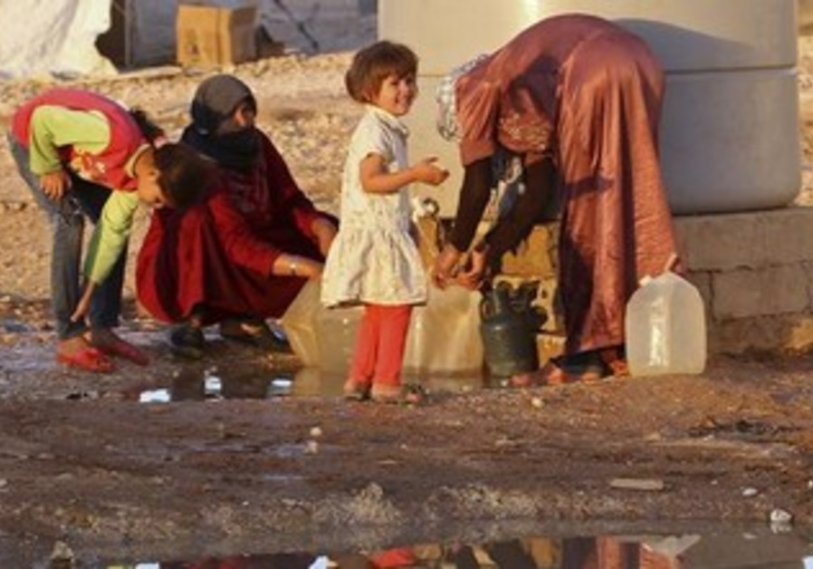 Syrian refugees collect water on  September 26, 2013.