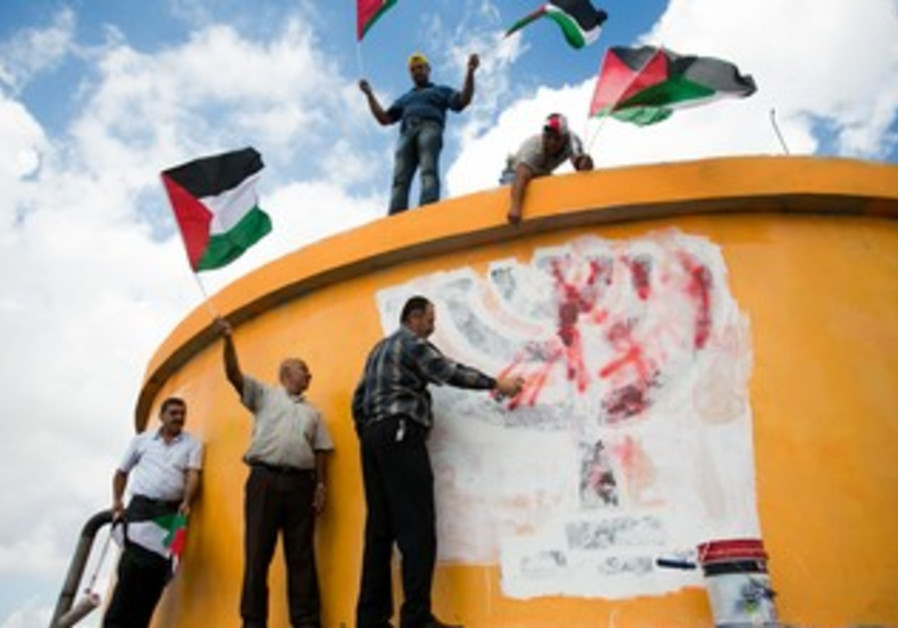 Palestinians wave flags on ruins of settlement