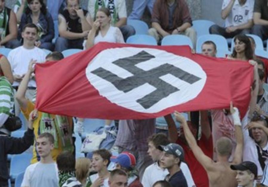 Soccer fans hold up Nazi swastika flag  [file]