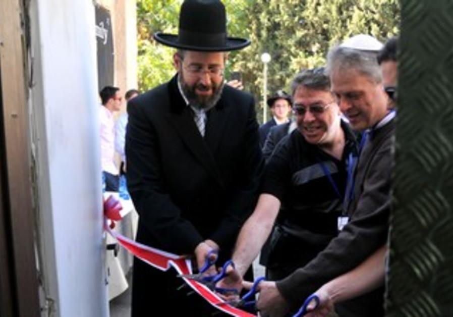 Chief Rabbi David Lau cuts ribbon at opening of Pantry Packers in Jerusalem, October 11, 2013.