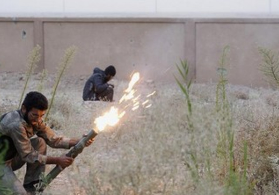 A Free Syrian Army fighter launches a rocket
