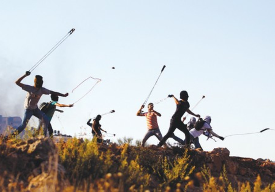 Palestinian youths slinging rocks.