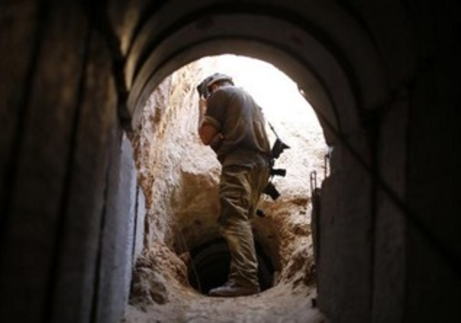 An IDF soldier looks into tunnel dug by Hamas for terrorism.