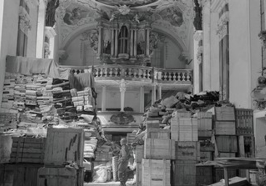 A US SOLDIER views art stolen by the Nazi regime and stored in a church in Germany in 1945.