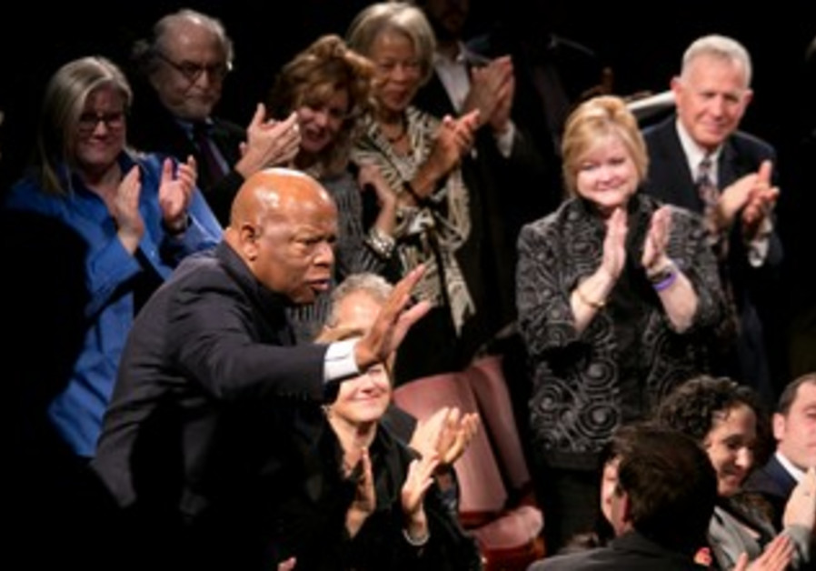 Representative John Lewis stands to applause, seated next to Daniel Pearl's sister, Tamara.