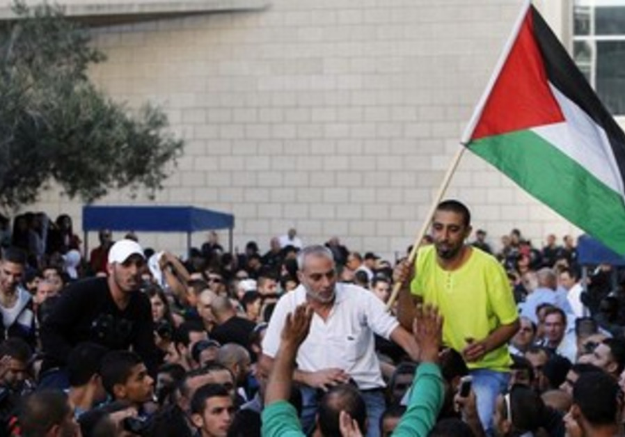 An Israeli Arab waves Palestinian flag during protest outside district court in Haifa, Nov 28, 2013.