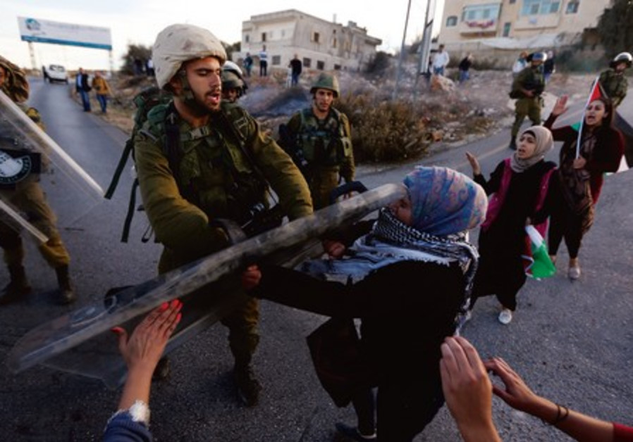 A soldier pushes back a Palestinian protester after protests against plans to resettle Beduin.