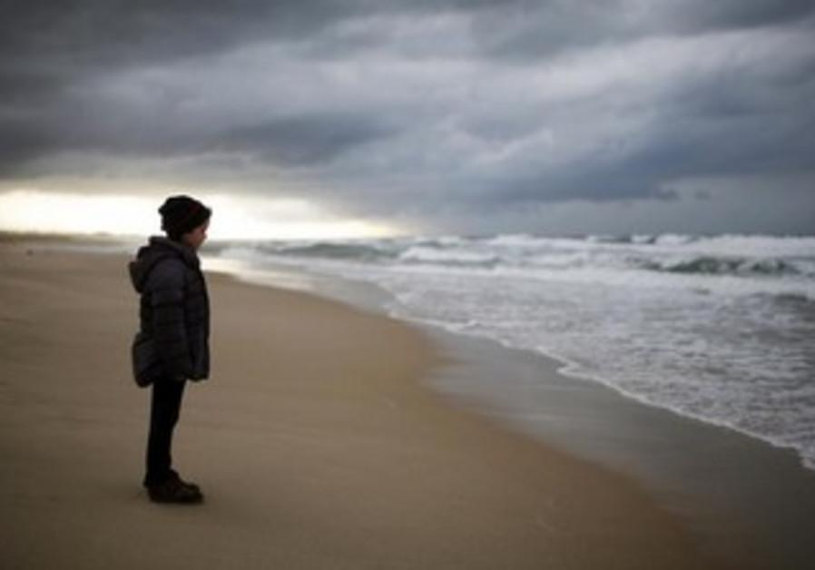 An Israeli girl stands on Zikim beach