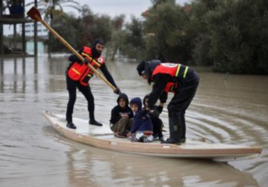 Palestinian civil defense evacuate kids after rain floods areas of the Gaza Strip, December 12, 2013