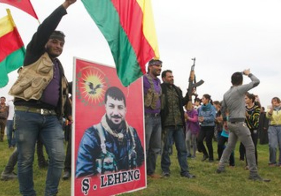 Residents and Kurdish fighters celebrate the liberation of their village from Islamist rebels.