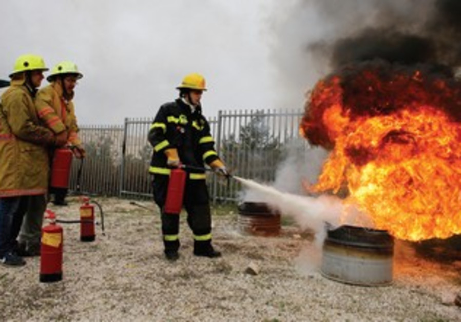 A FIREFIGHTER uses a fire extinguisher during a drill at a school in Jerusalem.