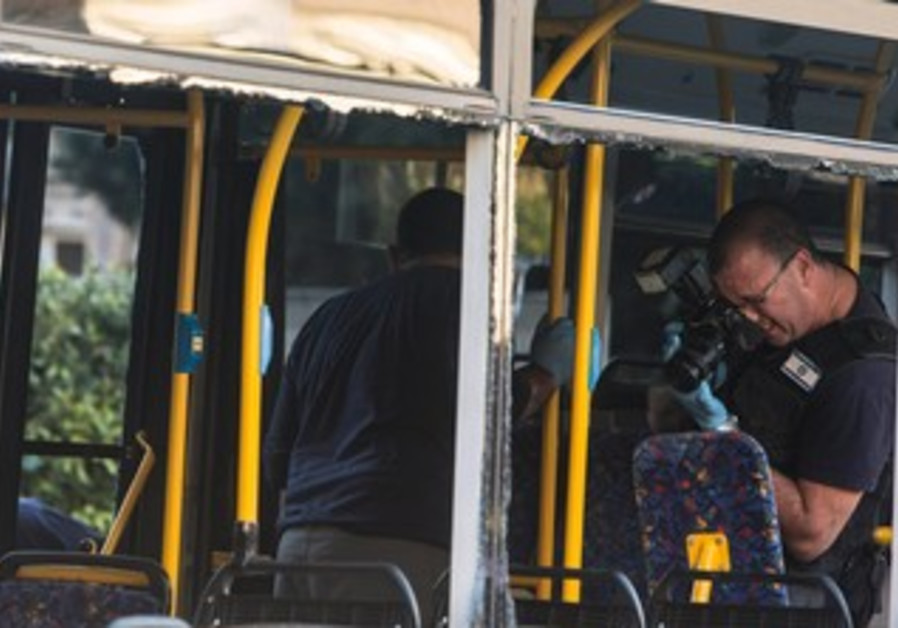 An Israeli police officer takes pictures inside a damaged bus at the scene of Bat Yam explosion