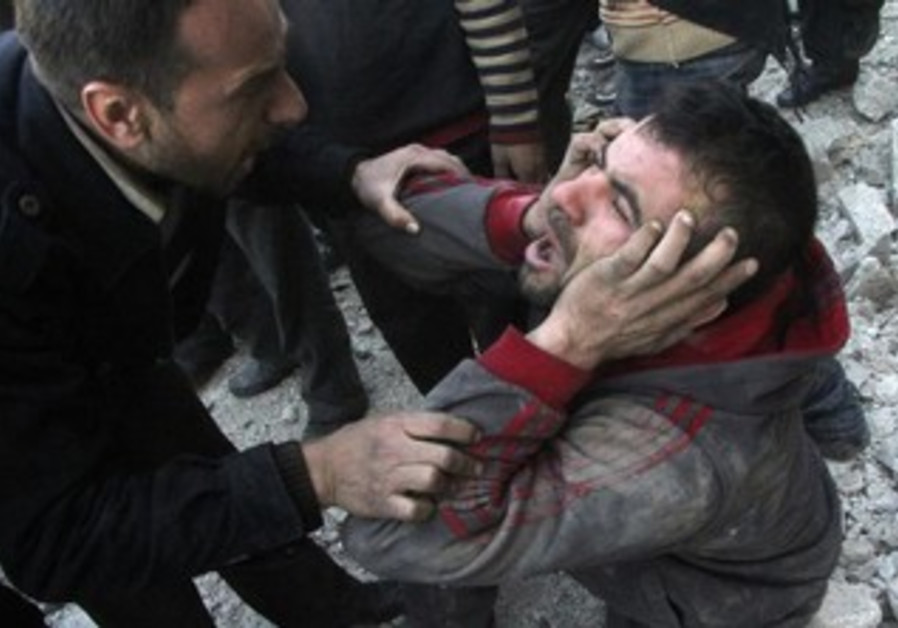 A Syrian man reacts after an air raid in Aleppo