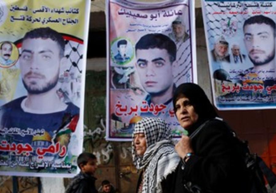 Gaza woman walks past posters of Palestinian prisoners